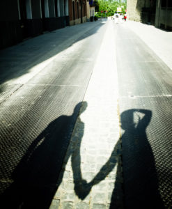 Shadow of two people holding hands while walking
