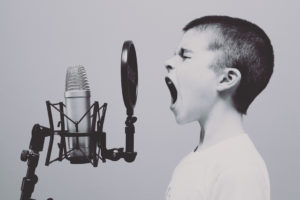 Boy speaking loudly in to a mic