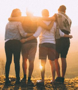 Four people embracing each other